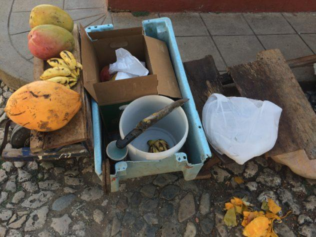 A makeshift fruit stand in Trinidad, Cuba with mangoes and bananas.