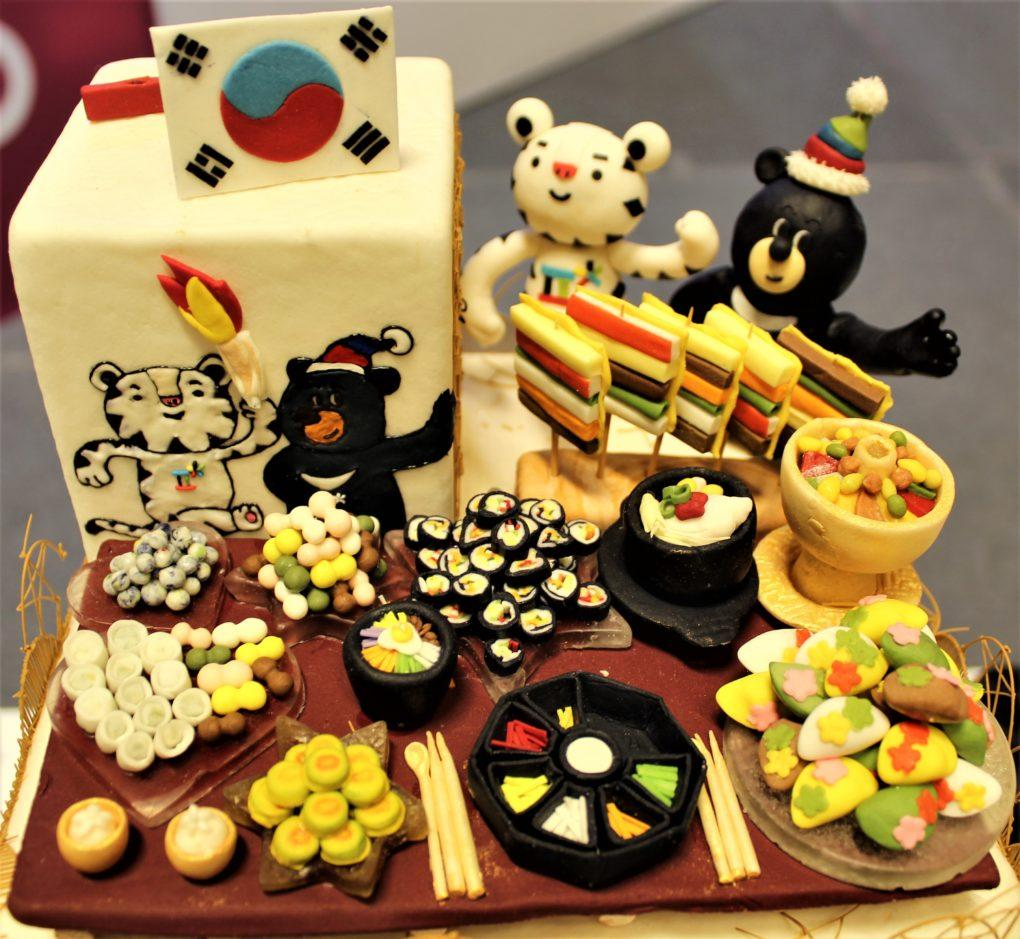 One of the amazingly detailed cakes from the Salon: the 2018 Olympic mascots sitting down to a Korean feast next to the Korean flag