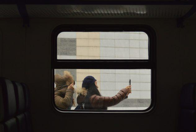 Girl Taking Selfie Through Train Window