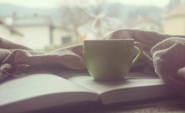 white cup of coffee on top of book
