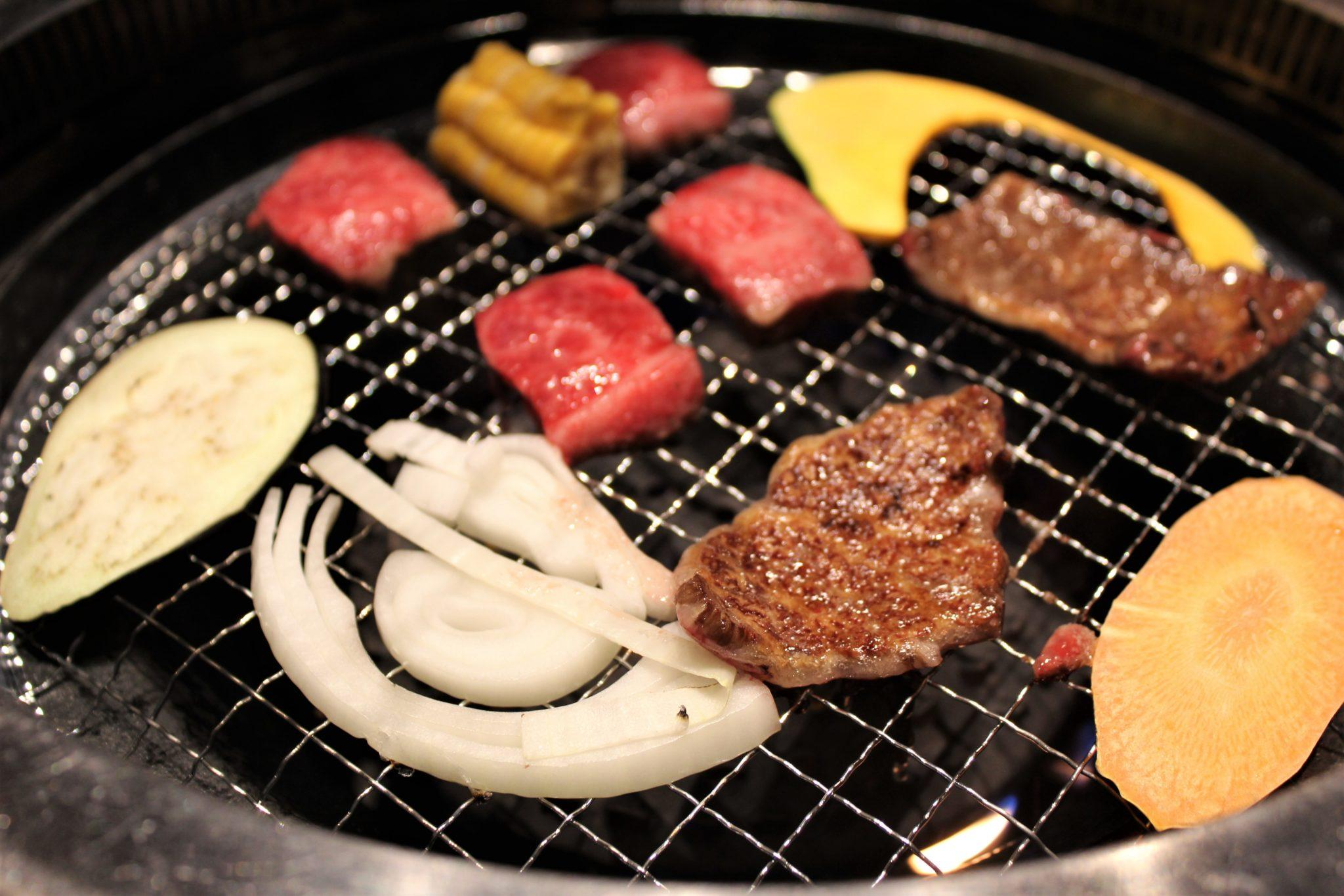 Affordable Kobe beef in Kobe shot of meat cooking on grill with vegetables